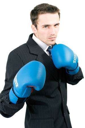 Handsome young man in suit and blue gloves boxing in office, made in studio isolated on white background photo