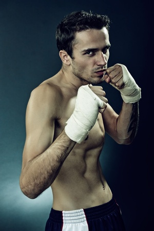 Handsome attractive young man boxing, made in studio on dark background photo