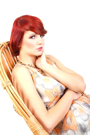 Portrait of beauty red hair female model sitting on wicker chair - made in studio on white background photo
