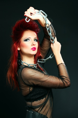 punk rock: Portrait of a sexy woman in black with chains