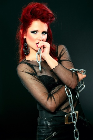 tough woman: Portrait of a sexy female model in black with chains - made in studio on black background Stock Photo