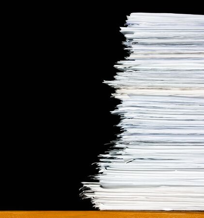 filing documents: stack of documents or files, overload of paperwork on black background