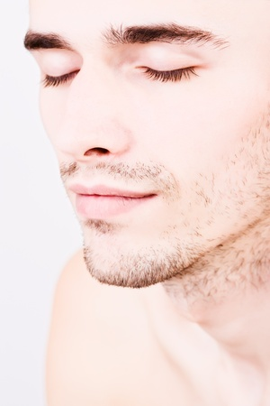sexual anatomy: Closeup portraiture of young handsome man with closed eyes made in studio on white background