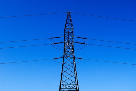 tall electric pylon on blue sky as background photo