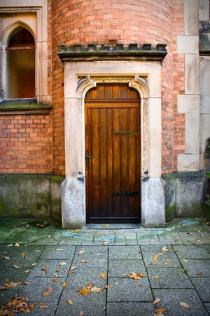 gothic window: wooden church door with stone surround and brick wall