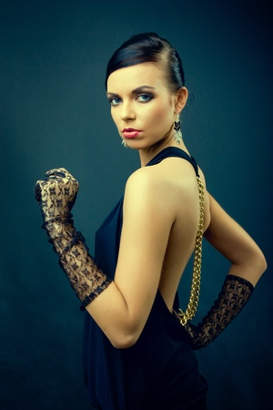 glamour model: elegance dark hair woman fashion with gloves on hands, studio shot on dark blue background  Stock Photo