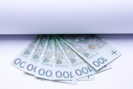 polish money: zloty, banknotes under roll of paper for text or design photo