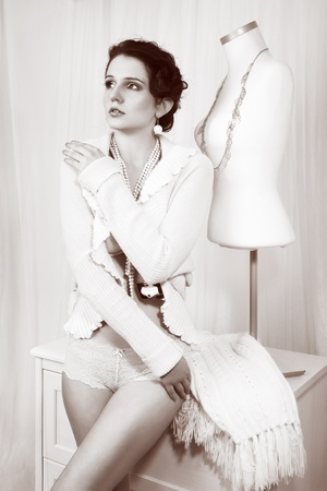 retro fashion woman as sewer near dummy, studio shot on bright background photo