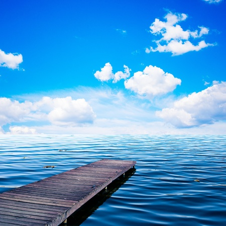 Wooden dock, pier, on a sea  ocean in summer sunny day, blue sky, white clouds photo