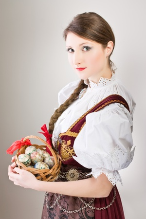 poland: Beauty woman in traditional Polish clothes holding wicker basket with Easter eggs, Cieszyn Silesia region, studio shot