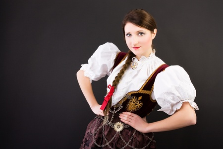 Beauty woman in traditional Polish clothes Cieszyn Silesia region, studio shot on black background photo