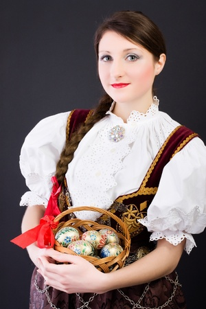 Beauty woman in traditional Polish clothes holding wicker basket with Easter eggs, Cieszyn Silesia region, studio shot photo