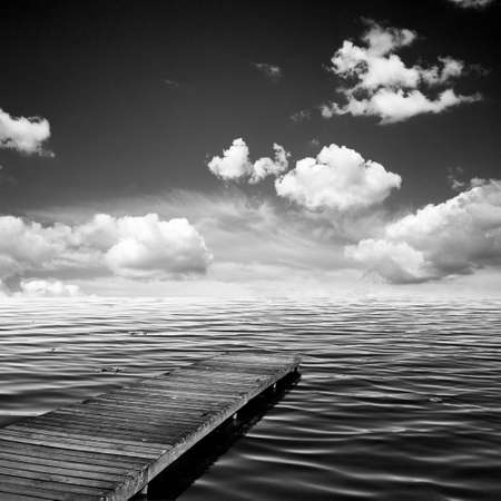 Wooden jar, pier on an ocean in summer, sky and clouds, black and white version photo