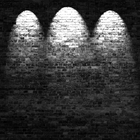 dark brick wall background in basement with beams of light photo
