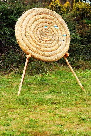 straw circle archery target with wooden arrows in it as competition concept photo