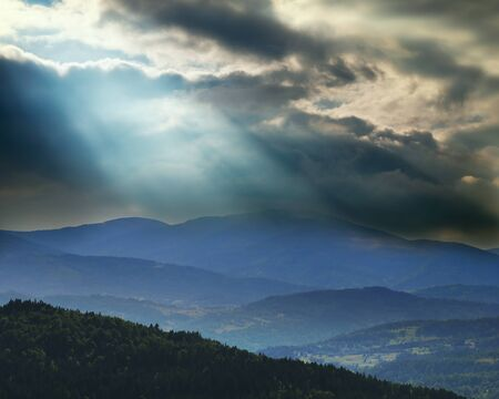 dramatic storm clouds over the mountains and beam of light illuminating the valley photo
