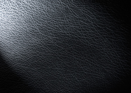 black leather texture background with spot light in the corner photo