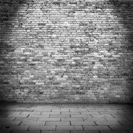 vignetted: brick wall texture background in basement and beam of lamp light Stock Photo