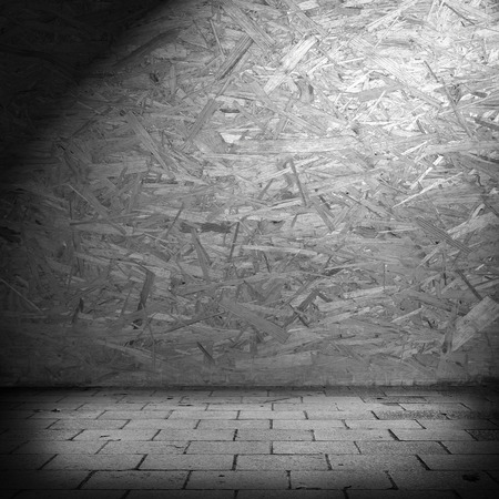 wood shavings: fiberboard wall texture background in basement and beam of spotlight Stock Photo