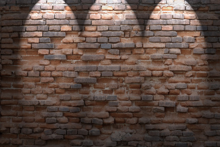 brick wall background: dark red brick wall background in basement with beams of spot lights
