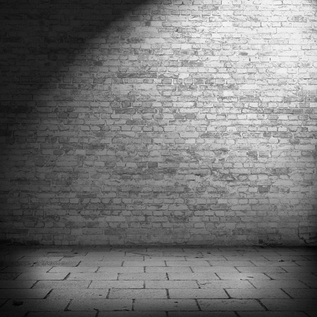 interior brick wall background texture in basement with beam of spot light photo