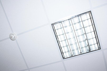fluorescent lamp: fluorescent lamp illumination and fire detector on modern office interior ceiling