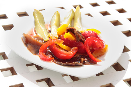 side order: side dish on white plate, vegetables salad made of dried tomatoes, pickled cucumbers and paprika