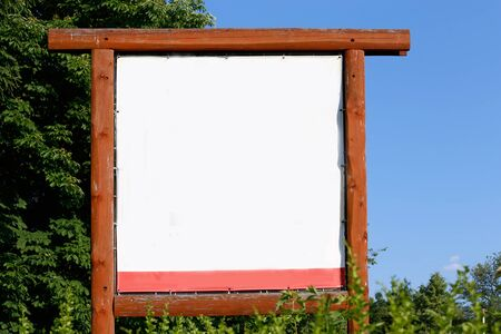 wood frame: whiteboard, empty billboard in wood frame on blue sky and trees background
