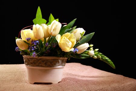 lowers: bouquet of yellow tulip flowers on the table, black background