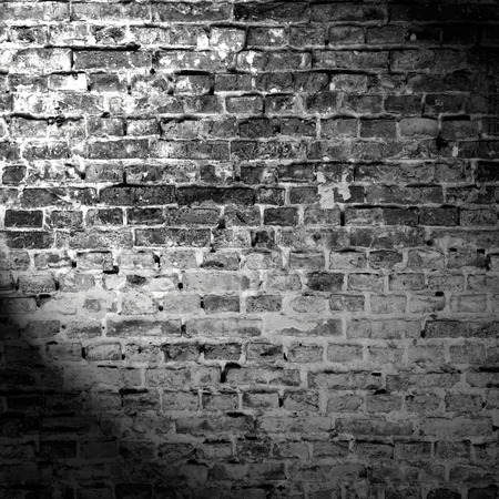bricks background: grunge background, black and white brick wall texture and beam of spot light highlight