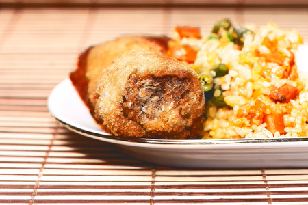 rise: croquet with meat and risotto with vegetables on white plate