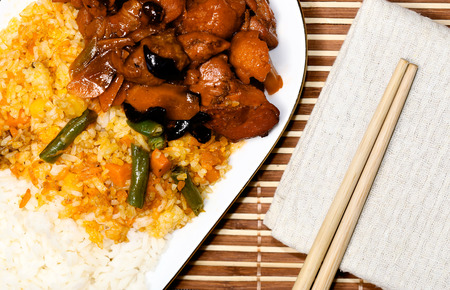 rise: chicken meat and risotto with vegetables and sushi chopsticks on beige cloth, asia food composition