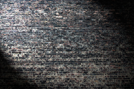 wall texture: grunge background, dark brick wall texture and beam of spot light highlight in the corner Stock Photo
