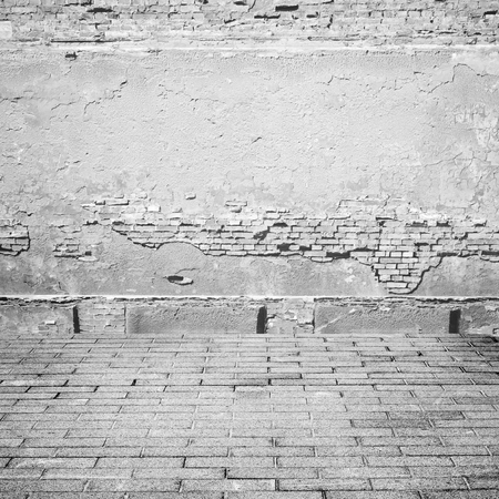 abandoned warehouse: black and white grunge background, brick wall texture plaster wall and tiled sidewalk abandoned exterior urban background for your concept or project Stock Photo