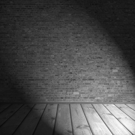 brick wall and wooden planks floor as black and white background interior background with black shadow and beam of spot light in the corner