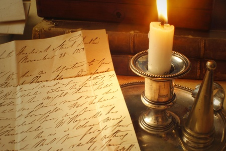 dickensian: reading old letter from 1800 bt candle light Stock Photo