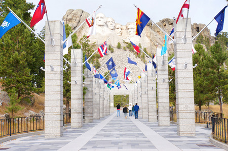 theodore roosevelt: George Washington, Thomas Jefferson, Theodore Roosevelt and Abraham Lincoln and the flags of the States at Mt. Rushmore National Memorial, Keystone, South Dakota, US Editorial
