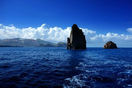 lipari: Aeolian Islands, two cliffs near Vulcano Island in the background, Tyrrhenian Sea, Sicily, Italy