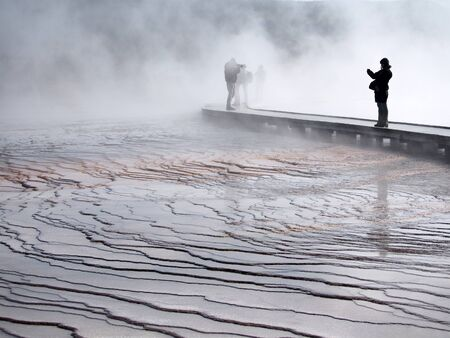 shadowy: Warm, wet mist hovers over boardwalk, concealing shadowy figures and dropping moisture on bridge. Thermal pools in Yellowstone National Park