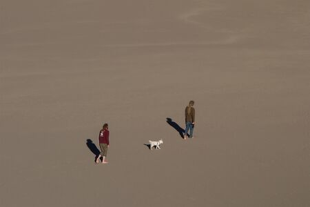 two men with a dog in the desert