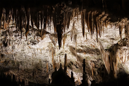 Postojna cave, Slovenia. Formations inside cave with stalactites and stalagmites. People travel by entertainment train in Postojna Cave. it is one of top Slovenian tourism sites.