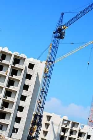 Building crane and building house against the blue sky. Building site photo