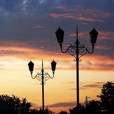 Retro street lamp on sunset sky background photo
