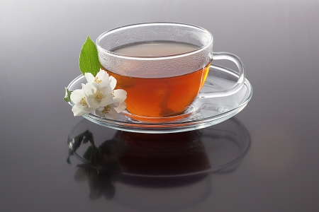 Transparent cup with green tea and  fresh  jasmine flowers on grey background photo