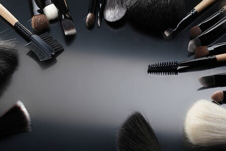 Collection of make-up brushes on black  background photo