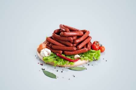 A composition of different sorts of sausages on the wood board with fresh vegetable photo