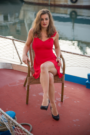 Beautiful brunette girl with red short dress, sitting on a fishing boat