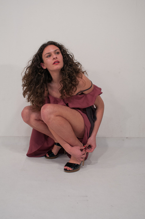 girl squatting mind laces her shoes, white background Foto de archivo