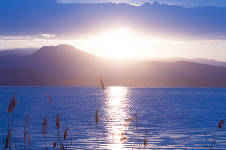 Sunrise on the lake. Panorama of the early morning. mountain in silhouettes and the rays of the rising. Sunrise on Lake Garda, Italy