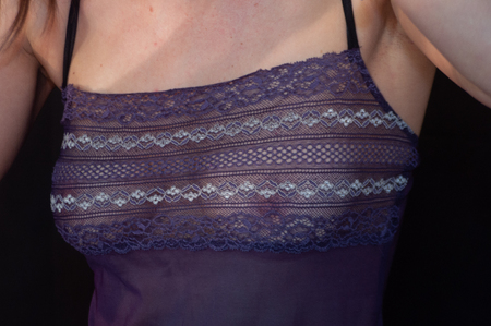Women's purple tank top in transparent lace. The breasts are seen in transparency. Unrecognizable woman.